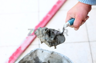 Construction worker is tiling at home