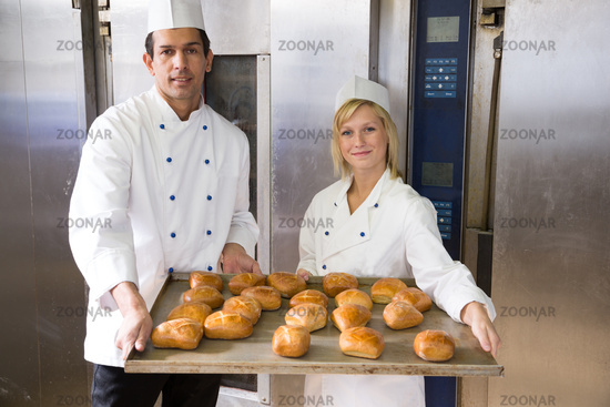 Bakers with tablet of bread in bakery or bakehouse