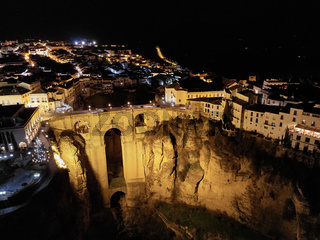 Aerial photo drone point of view huge gorge and ancient architecture, city street lights night view of Ronda in Spanish province of Málaga. Costa Blanca. Spain