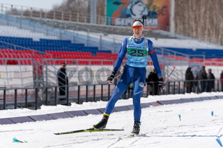 Russian sportsman biathlete Danil Ageev in action skiing on ski track distance biathlon stadium. Junior biathlon competitions East of Cup