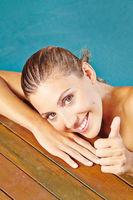Schöne Frau im Schwimmbad hält Daumen hoch