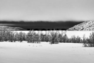 Schlechwetter ueber dem gefrorenen See Tornetraesk, Lappland