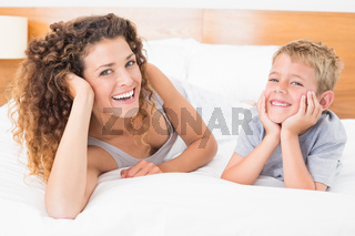 Happy mother and son lying on bed looking at camera