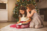 Two girl friends writing a letter to Santa