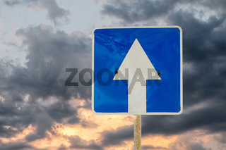 Big white arrow -  directional road sign outdoors against sunset sky