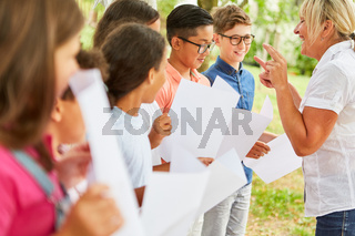 Lehrerin und Kinder zusammen bei der Chorprobe