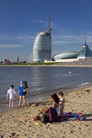 People at Weser strand bad with the Atlantic Hotel Sail City in the background, Bremerhaven, Germany