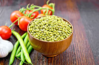 Mung beans  in bowl with vegetables on board