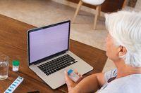 Senior caucasian woman on video consultation holding medicine