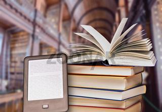 Bücherstapel und E-Book-Reader in einer Bibliothek