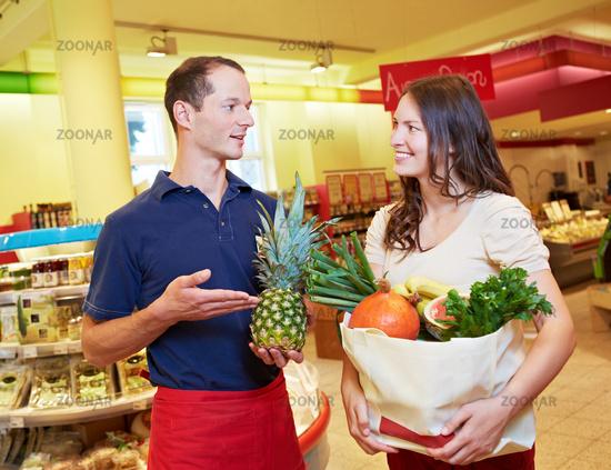 Verkäufer empfiehlt Ananas im Supermarkt