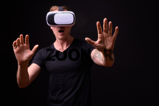 Portrait of young handsome man using virtual reality headset
