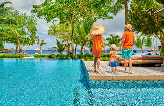 Family of three by poolside. Resort swimming pool at Seychelles.