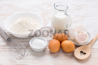Assortment of basic baking ingredients for cake or pancakes on wooden background