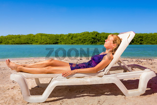 Dutch woman sunbathing on beach by sea
