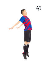Young soccer player jumping to stop ball by chest