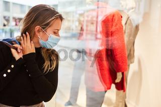 Kundin mit Maske vor einem Schaufenster mit Mode