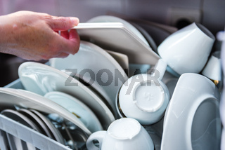 Woman loading dishes and silverware into dishwasher in the kitchen