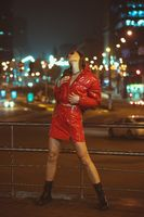 Full-length portrait of young girl with glasses outdoor fashion portrait with braided hair wears red down jacket and fashion on neon street lights. Night club fashion. Girl and neon lights