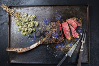 Barbecue dry aged wagyu tomahawk steak with herbs as top view on black rustic board