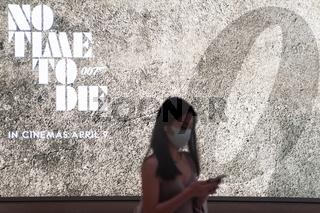 Singapur, Republik Singapur, Frau mit Mundschutz vor einer Werbung fuer James Bond Film