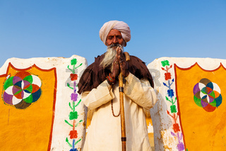 senior indian man in front of his  traditional village house, Jaisalmer, India