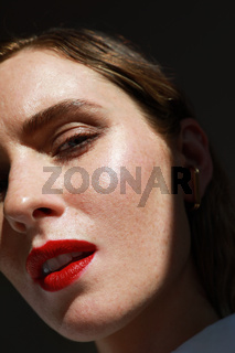 Caucasian young woman with red lips. Vertical close-up of beautiful woman.