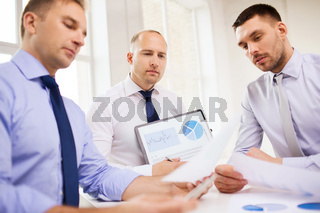 serious businessmen with papers in office