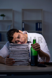 Alcohol addicted businessman working late in the office