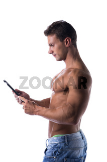 Shirtless young male bodybuiler holding ebook reader or tablet PC