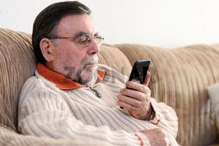 Elderly Man Using Cellphone Sitting On Sofa At Home, during Coronavirus quarantine.