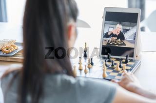 Zwei Frauen spielen Schach im Videochat online