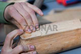 Human hands pressing two pieces of old wooden furniture together that were glued with bone glue