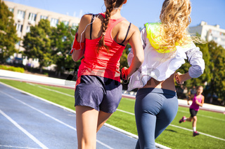 Runners on the stadium track. Women summer fitness workout