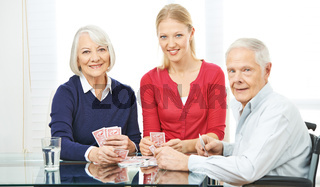 Familie mit Senioren beim Karten spielen