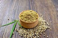 Flour hemp in bowl of grain and leaf on board