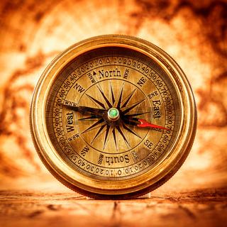 Vintage compass lies on an ancient world map.
