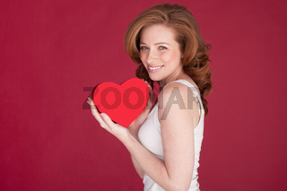 female with red hair holding heart shape