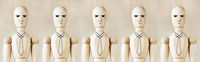 Wooden puppets as impersonal office staff stand in a row
