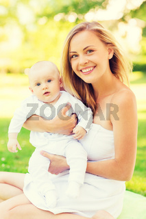 happy mother with little baby sitting on blanket