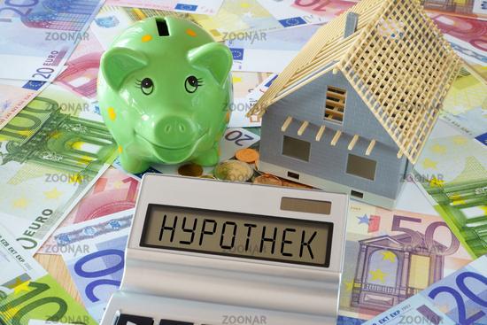 Das Wort Hypothek auf Display von Taschenrechner und Sparschwein