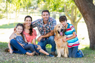 Happy family with their dog in the park