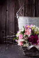 Pink bouquet from gillyflowers and alstroemeria in the basket on old wooden background with metal bucket