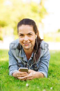 smiling young girl with smartphone and earphones