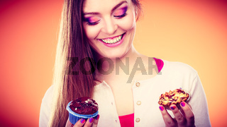 Smiling woman holds cakes cupcakes  in hands