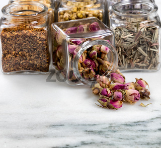 Spices and herbs in small glass jars pouring onto white marble stone background