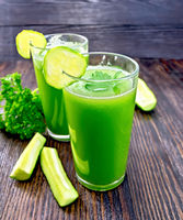Juice cucumber in two tall glass on dark board