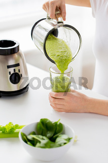 close up of woman with blender jar and green shake