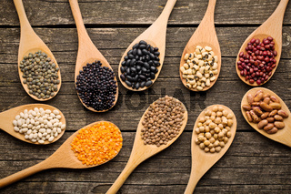 various dried legumes in wooden spoons