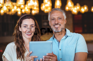 Happy couple smiling at camera and using tablet